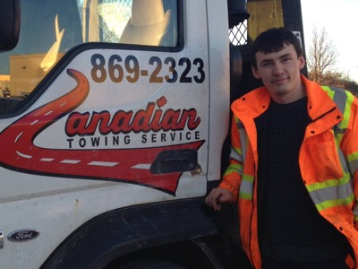 Demir Ahmeti, the owner of Canadian Towing in Ottawa, standing next to one of his two trucks