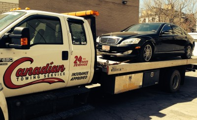 A Mercedez Benz being towed by a flat bed tow truck in Ottawa